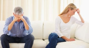 Upset married couple sitting on the sofa after a disagreement
